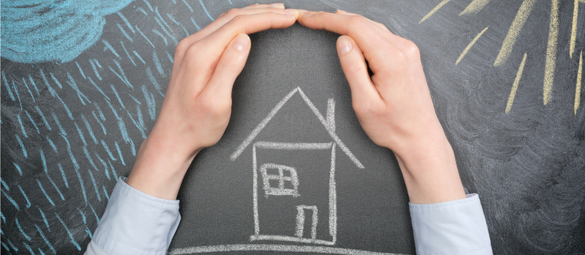 Hands cupped around the chalk picture of a house