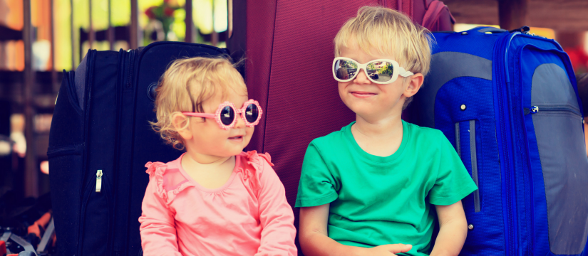 Two pre-schoolers wearing sunglasses, sitting next to luggage.
