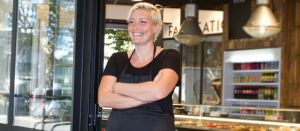 Woman standing in front of her bakery shop